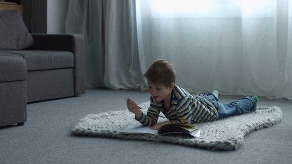 Thumbnail for Little Boy Drawing While Lying on Floor at Home