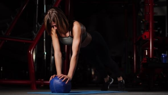 Cover Image for A Brunette Athletic Builds Push-ups on a Mache in the Gym