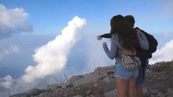 Thumbnail for Young Couple of Tourists Standing at the Top of Mountain and Looking at Beautiful Landscape Forward