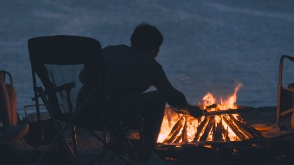 Cover Image for A Man Is Sitting in an Armchair Near Bright Fire on a Nightly Coast