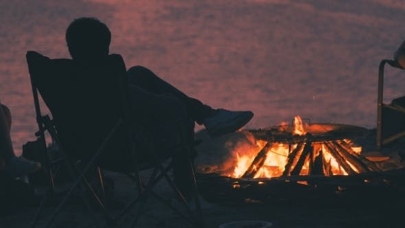 Cover Image for Silhouette of a Man Is Sitting in an Armchair Near Campfire on a Nightly Coast Оn the Sunset