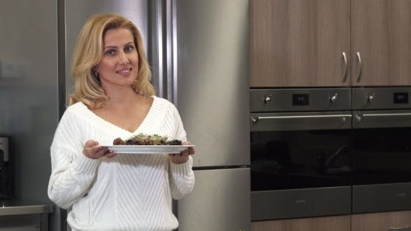 Thumbnail for Beautiful Mature Woman Smiling To the Camera Posing with a Dish After Cooking