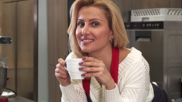 Thumbnail for Happy Mature Woman Smiling Having Coffee Resting After Cooking at the Kitchen
