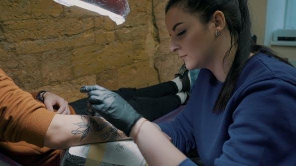 Thumbnail for Brünette weibliche Tätowierer in Violett Kleidung machen Tattoo auf dem Arm des Mannes Ihr Klient mit Pistole in