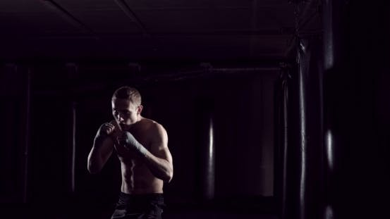 Kickboxer Shadow Boxing As Exercise for the Fight Fighter Training Punching Boxing in the Darknes