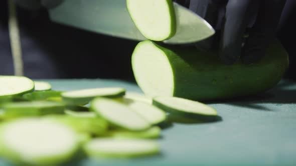 Thumbnail for Cook's Hands in Black Gloves Slicing Zucchini Close Up Selective Focus