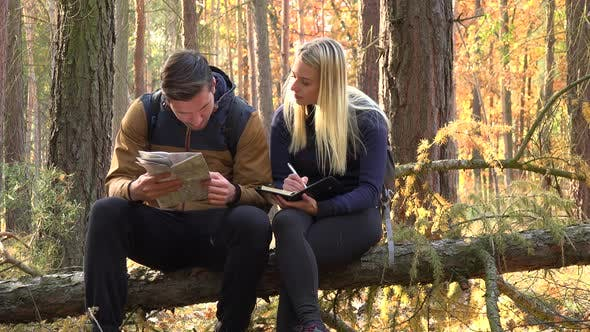 Thumbnail for A Hiking Couple Sits on a Broken Tree in a Forest, Man Reads Off a Map and the Woman Writes Notes