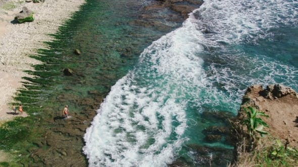 Cover Image for Aerial Topview Family of Three People Come Into the Sea Water in Balangan, Bali, Indonesia