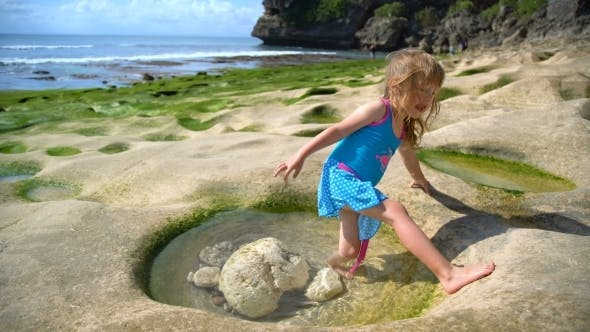 Cover Image for Little Adorable Girl Stands in a Volcanic Hole with Water at the Rock Beach Balangan in Bali