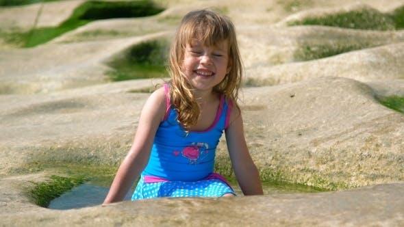 Thumbnail for Happy Little Girl Fun Play Splashing with Water on the Volcanic Beach Balangan in Bali