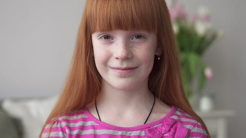 Little Happy Ginger Girl with Freckles Smiling in a White Room