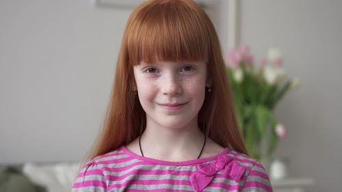 Little Red-haired Girl with Freckles Smiling in a White Room