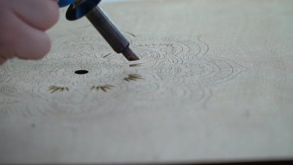 Thumbnail for Girl Burns a Pyrograph on a Tree Pattern