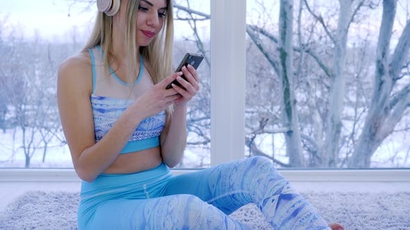 Cover Image for Girl with Mobile Phone in Hands Enjoys To Music Through Headset Sitting By Window