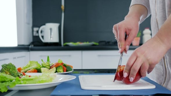 Cover Image for Hands of Woman with Knife Slicing Sweet Red Pepper for Salad on Cutting Board, Healthy Food