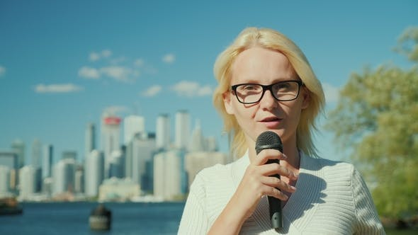 Thumbnail for A Woman Journalist and TV Presenter Speaks Into a Microphone on a City Background. Toronto, Canada