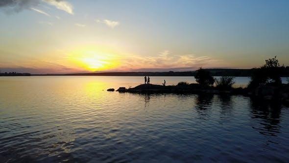 People Enjoying the Riverside Sunset