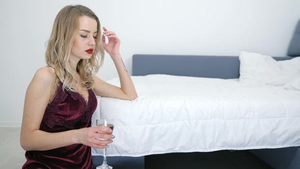 Cover Image for Disappointed Girl Having Headache in Sexy Sleepwear on Floor with Champagne Glass in Room