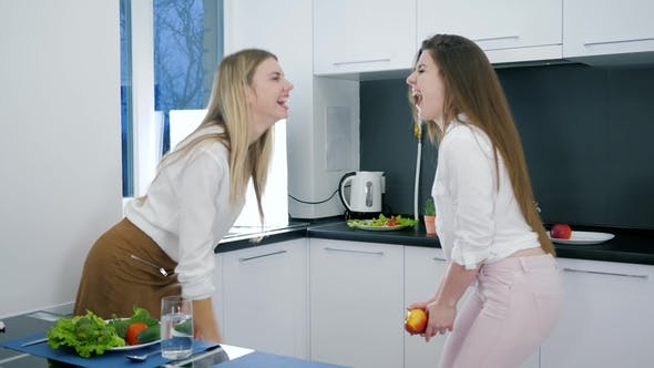 Thumbnail for Happy Girlfriends with Products in Hands Dancing and Laughing During Cooking on Background Kitchen
