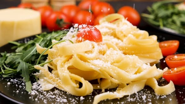 Cover Image for Parmesan Cheese Falling in Plate with Tagliatelle Pasta