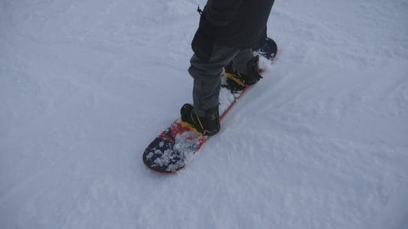 Thumbnail for Feet of snowboarder sliding on snowy slope in mountain. Young man learning to ride on hill