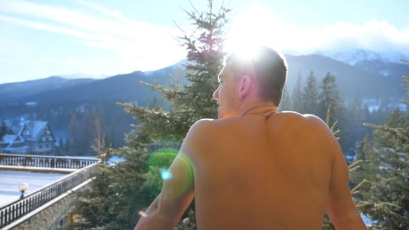 Thumbnail for Young Athletic Guy Standing on Balcony and Breathing Fresh Air During Winter Day at Mountains