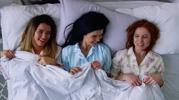 Thumbnail for Top View, Three Beautiful Girlfriends Girls Go To Bed in Cute Pajamas on the Bed and Put on Eye