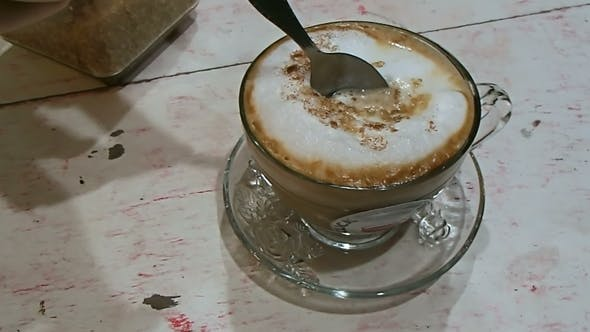 Thumbnail for Woman Stirs Hot Cappuccino with a Spoon Tasty Coffee in Transparent Cup. Street Cafe in Bangkok