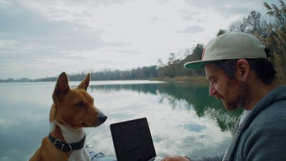 Thumbnail for Freelancer Works on His Laptop Outdoor Next to Lake, Sitting on Pond