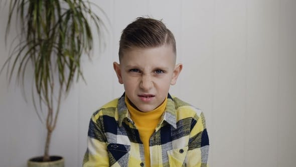 Thumbnail for Portrait of Beautiful Angered 7- 8 Years Boy Who Sits on the Floor Over White Wall Background