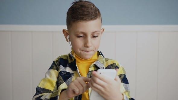 The Boy Blonde hört Musik in Kopfhörern und spielt ein Online-Spiel am Telefon zu Hause