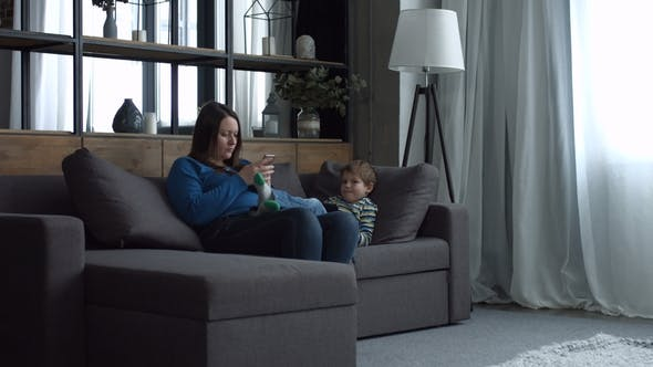 Thumbnail for Mom and Kid Relaxing on Couch with Digital Devices