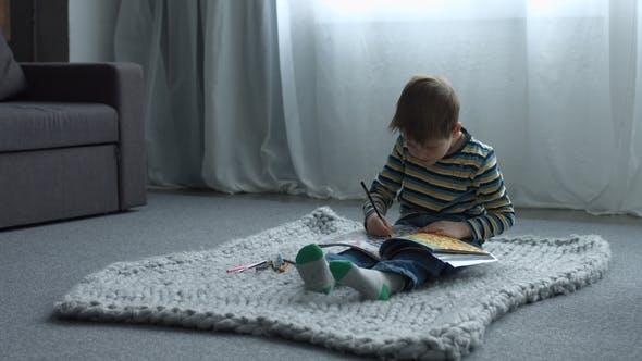 Thumbnail for Konzentrierte niedliche Jungen Zeichnung in Kind Labyrinth Buch