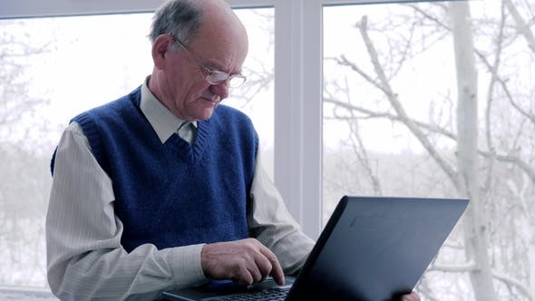 Thumbnail for Older Man and Woman with Laptop Spend Time on Internet on Vacation in Room
