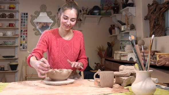 Thumbnail for General View of a Girl Ceramist Smoothing the Clay Pot Surface Using the Tassel in the Pottery