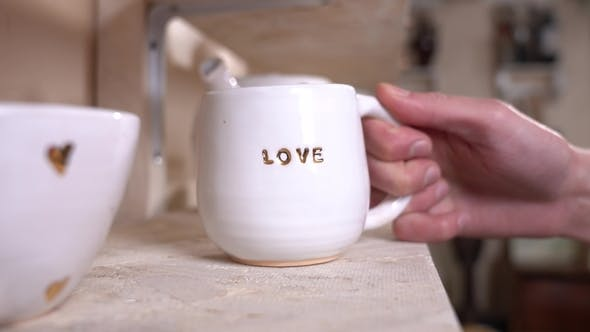 "Thumbnail for Happy Girl Putting a Pure White Cup Titled with Gold Letters ""LOVE"" Text on the Shelf."