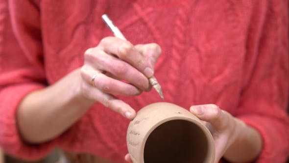 Thumbnail for of Female Ceramist Putting a Decoration Using a Knife Tool on the Raw Clay Cup in Her Hands.