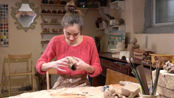 Thumbnail for General View of a Girl Ceramist Fine-tuning the Raw Clay Cup in the Pottery Workshop.