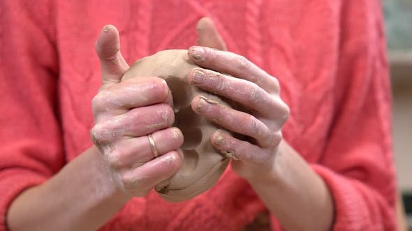 Thumbnail for Girl Ceramist Kneads in Hands a Lump of Clay Before Making a Craft From It.