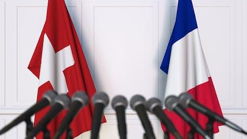 Flaggen der Schweiz und Frankreichs bei der Internationalen Pressekonferenz