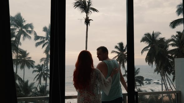 Silhouette of Couple in Love on Terrace Looking at the Sea