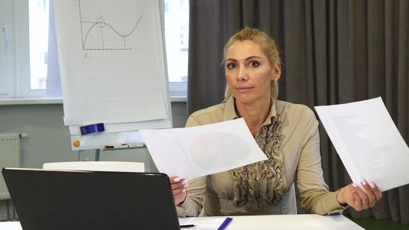Cover Image for Mature Business Woman Looking Confused While Examining Documents