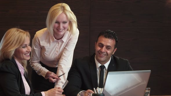 Three Business People Are Actively Discussing What They See in Their Laptop