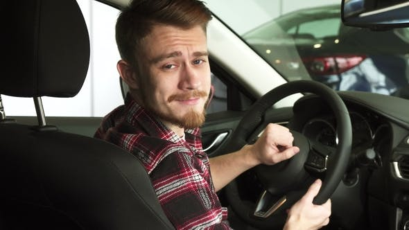 Cover Image for Attractive Bearded Man Smiling to the Camera Over his Shoulder Sitting in a New Car