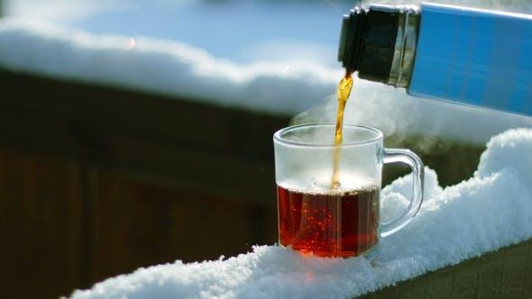 Tee Gießen Sie nach unten in Glas stehend auf Schnee am Baumzweig
