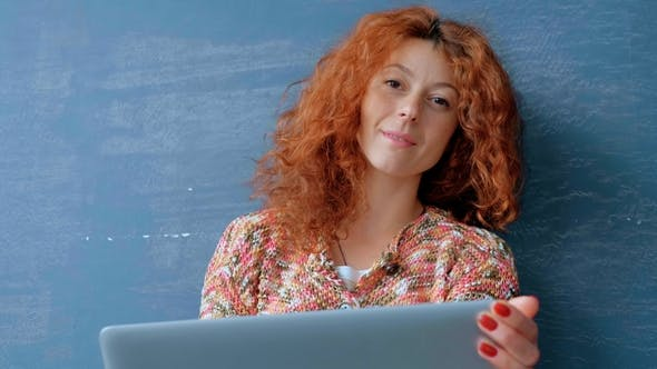 Thumbnail for Portrait of a Woman with a Red Hair Working on a Laptop