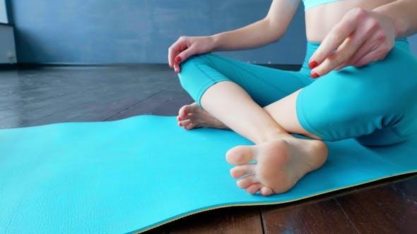 Thumbnail for Eine Frau entfaltet einen Teppich zum Üben von Yoga im Studio.