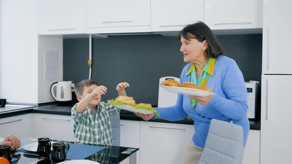 Cover Image for Food Time, Grandmother Brought Delicious Bakery Products on Plate for Boy and Granddad Sitting at