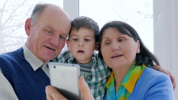 Cover Image for Happy Pensioner Family Uses Mobile Phone To Communicate on Internet in Room