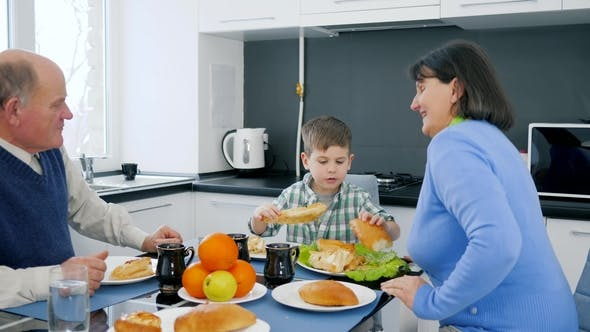 Cover Image for Pensioner Senior Couple Hugging Child at Lunch Time in Kitchen Near Table with Delicious Food